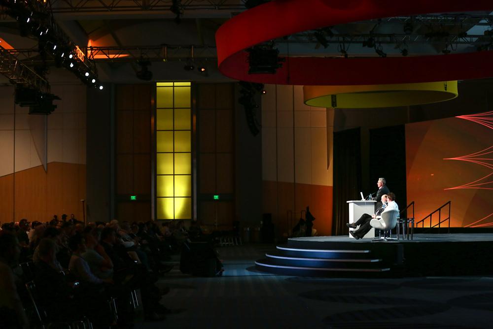 Three men presenting on a dark stage.