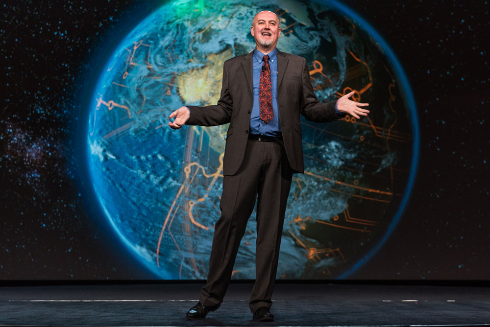 Man giving a presentation in front of an image of earth.
