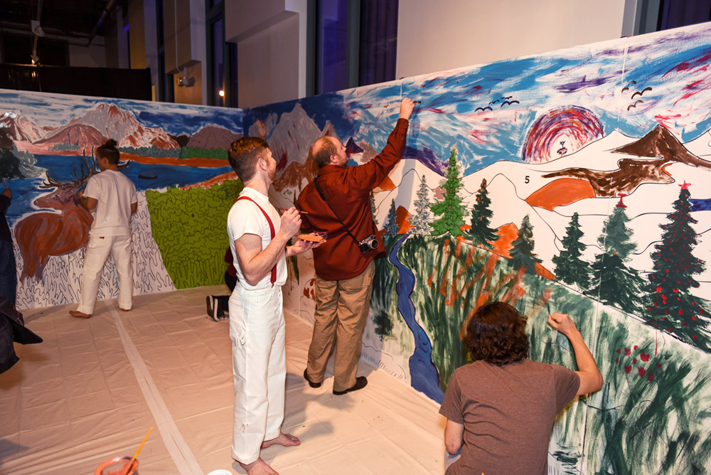 People help paint a large mural of mountains and trees.