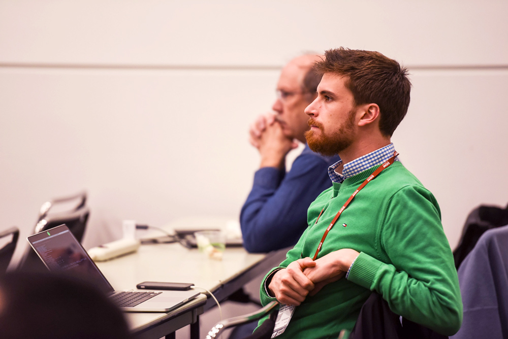 Man in a green sweater sits and listens to a presentation.